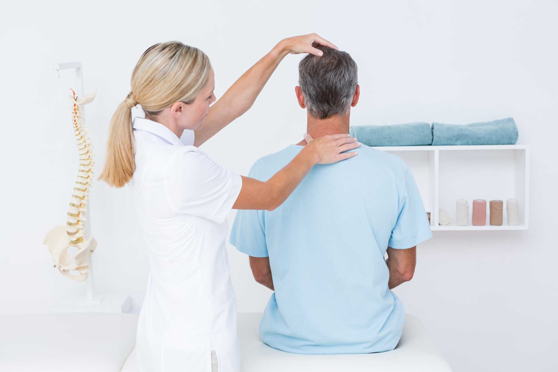 Female chiropractor checking alignment of man's neck.