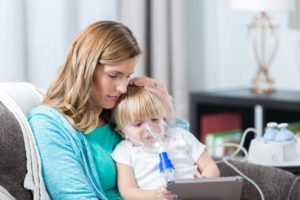 Toddler boy with nebulizer sitting on mom's lap playing with tablet