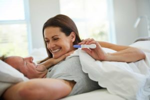 couple in bed, happy with pregnancy test results